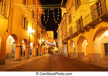 Town center at evening. Alba, Italy. - Narrow paved street...
