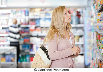 Young Woman Shopping At Supermarket - Young Caucasian woman...
