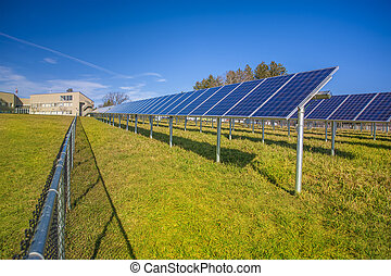 Solar panels in field with blue sky used to furnish...