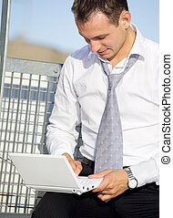 city life - handsome businessman with laptop computer in the...