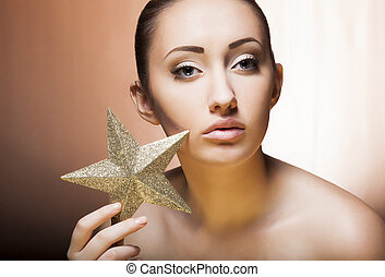 Woman with golden star. Beautiful professional holiday make-up