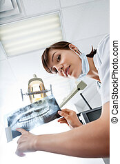 Young Female Dentist Pointing At X-Ray Image - Low angle...