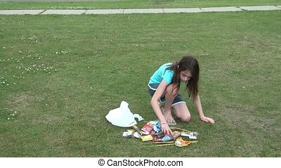 Girl Opening Fireworks Bag - Young girl opening bag of...