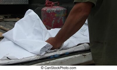 Folding Up Construction Plans - Man folds up construction...