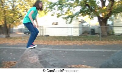 Girl Jumping Onto Rocks in Fall - Girl jumps onto large...