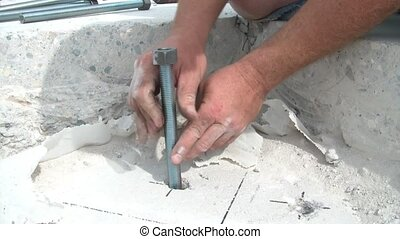Gluing Bolts into Concrete - Construction shot revealing a...