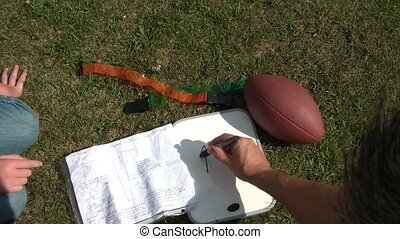 Football Play Gameplan in Grass - Drawing up football play...