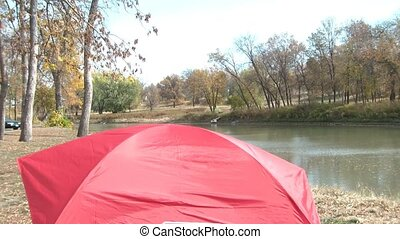 Camping Next to River with Tent - Red tent is set up next to...
