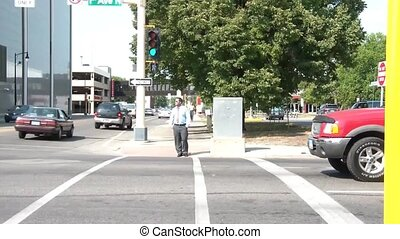 Businessman Walks Across Street - A business man dressed...