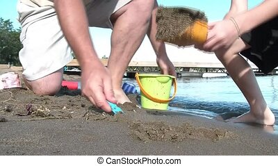 Father and Son Dig Sand at Beach