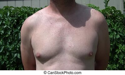 Flexing Pecks in Sun - Man is flexing pectoral muscles in...