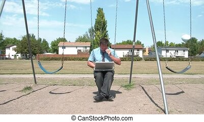 Businessman Swinging at Playground with Laptop - Businessman...