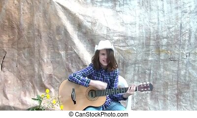 Cowgirl Playing Guitar in Sun - Cowgirl is playing guitar in...