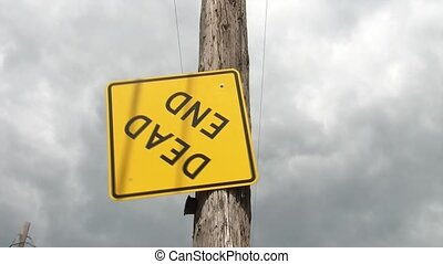 Dead End Sign Upside Down - Yellow dead end sign swings from...