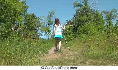 Girl Hiking Up Hill with Stick - Girl hikes up a hill...