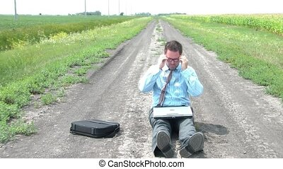 Businessman Sits on Dirt Road Using Laptop - Businessman is...