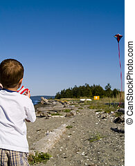 Kite Flying - A young boy flying a kite at the beach on a...