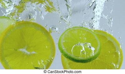 lemon and limes - limes and lemon dropped in water