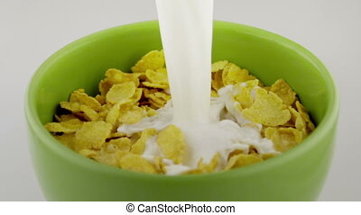 cereals with milk - milk falling into a green bowl of...
