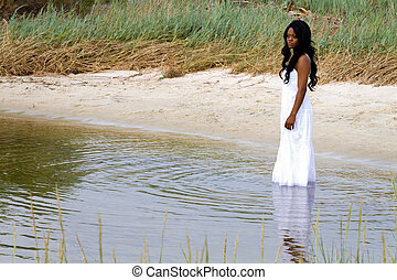 Woman In Water - Lonely African American woman stands...
