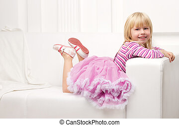 Little girl posing happily on sofa - Little cute girl posing...