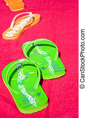 Flipflops - Two pairs of flipflops on red beachtowel. Symbol...