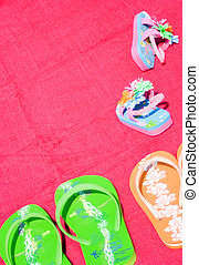 Family Flip Flops - Three pairs of flip flops on a red beach...