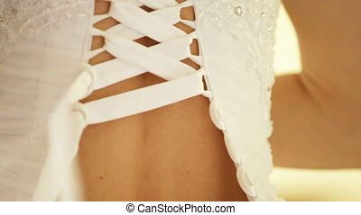 Lacing up a corset of a wedding dress