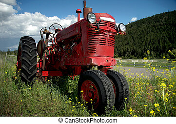 Old Red Farm Tractor - An old red farm tractor resting in a...