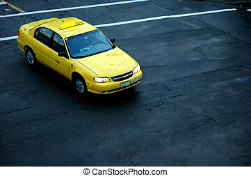 Yellow Taxi cab - A yellow taxi cab on a wet city street.
