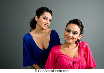 blue and pink - two latinas with contrasting dark blue and...