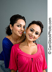 pair of attractive latinas smiling in colorful blouses