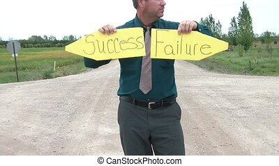 Intersection of Success and Failure - Businessman holds up...