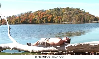 Guy Tans Body Laying on Driftwood in Fall Season - Man...
