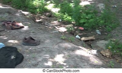 Homeless Camp by River - Homeless persons camp with items...