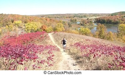 Jogging Uphill in Fall Landscape - Man jogs up trail on...
