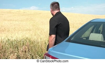 Leaning Against Car at Wheat Field - Man in black leaning...