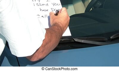 Leaving Note Under Windshield - Man in sun writes in black...