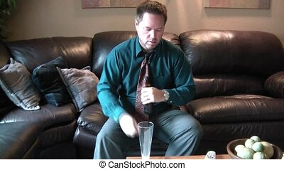 Tired Man Drinks Beer After Work - Businessman sits down on...