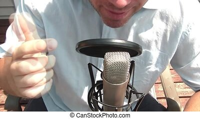 Man Behind Microphone Talks - Man behind shiny silver...