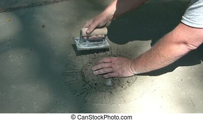 Man Smoothes Out Cement with Trowel - Worker rounds out...