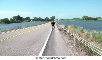 Man Walking on Road Between Lakes - Guy walking on shoulder...