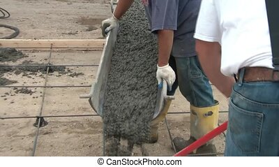 Men Pour Concrete into Driveway - Workers pour wet concrete...