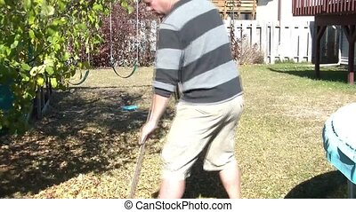 Man Raking Leaves in Fall - Man rakes leaves in backyard...