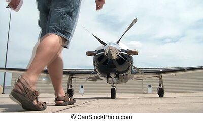 Man Spins Propeller on Airplane - Man approaches large shiny...
