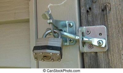 Opening Padlock with Key - Hand opens up padlock with key at...