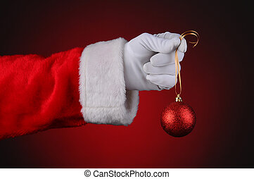 Santa Hand Holding Red Ornament - Santa Claus hand holding a...