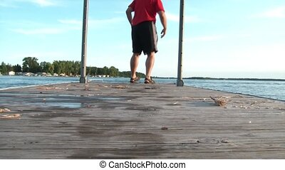 Man Walks to End of Dock & Sits