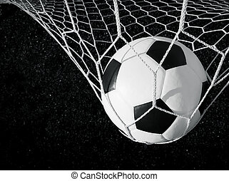 Soccer ball in goal, black and white