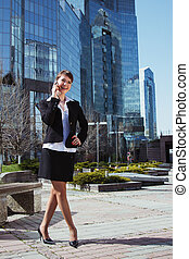 Portrait of a cute business woman over business center on back